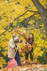 Hispanic couple playing with autumn leaves
