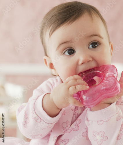 Mixed race baby girl chewing on plastic toy