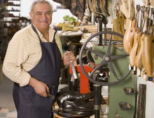 Hispanic cobbler in shoe repair shop