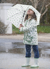 Mixed race girl with umbrella in rain