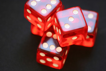 Five red dice in a pile on a dark gray background