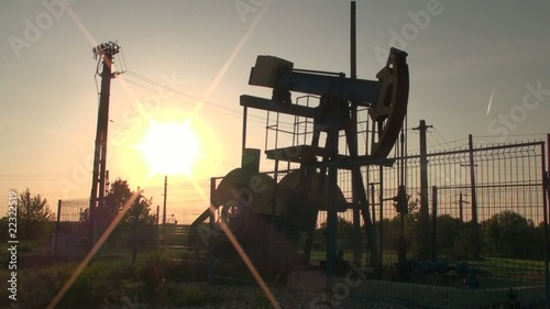 An oil pump jack in action at sunset – backlight