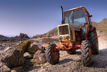 Old, rusty tractor on a pebble beach
