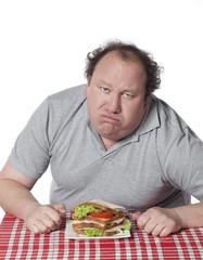 homme obèse devant un sandwich vitaminé