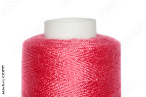 Fragment of coil with red threads isolated on white background