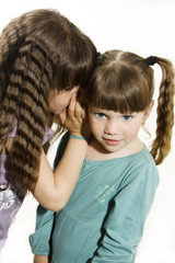 Two little girls telling secrets, isolated