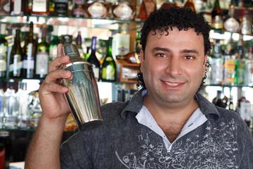 Barman with shaker behind bar rack.