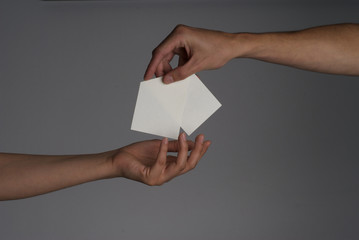 Two hands of man and woman with a piece of paper