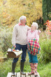 Senior Couple Outdoors With Picnic Basket By Autumn Woodland