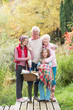 Grandparents With Grandchildren Carrying Picnic Basket By Autumn