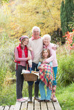 Grandparents With Grandchildren Carrying Picnic Basket By Autumn poster