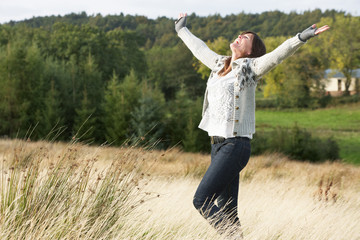 Young Woman Enjoying Freedom Outdoors in Autumn Landscape