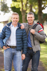 Two Male Friends Walking Outdoors In Autumn Park Together