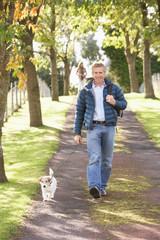 Man Walking Dog Outdoors In Autumn Park