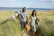 Young Couple Carrying Picnic Basket And Windbreak Walking Throug