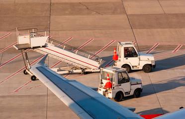 Airport. Trucks and ladder near airplane.