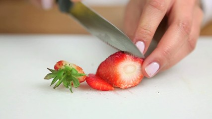Woman chopping a strawberry