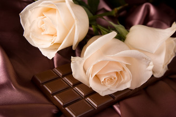 White roses on brown silk and chocolate
