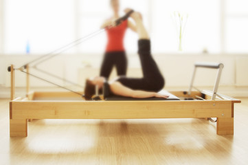 Plilates reformer in use by two women, soft focus
