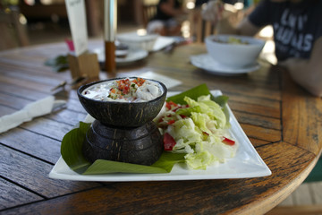 Ceviche with raw fish in coconut milk and salad