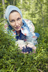 Young woman plucks bilberry in forest..