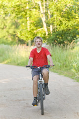 Teenager goes on bicycle on country road