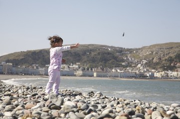 Toddler throwing pebbles on the beach
