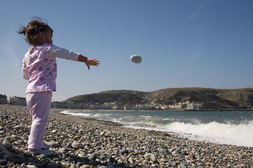 Little girl happily throwing pebbles into the sea