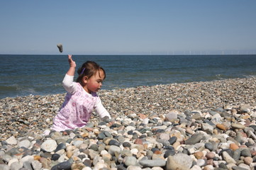 Cute baby throwing stones over her head