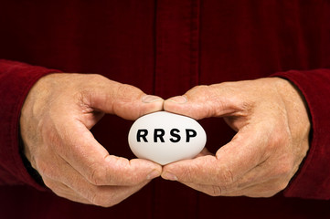 RRSP written on an egg held by man