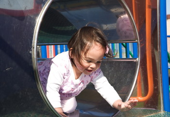 Little girl playing on a park play frame