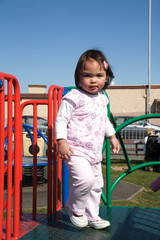 Baby girl playing on a park play frame