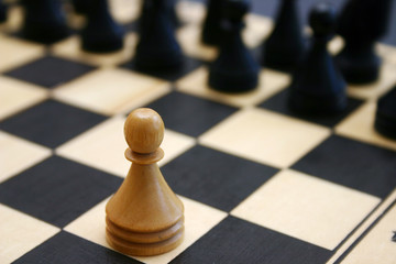Wood chess game shows white brave pawn challange stronger enemy.