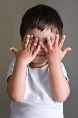 bambino che gioca con le mani in viso