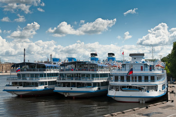Several white cruise liners are moored in river port.