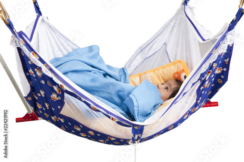 Baby Sleeping in a traditional, hammock-style cradle, isolated