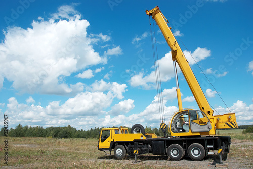 mobile crane with risen boom outdoors - 22435907