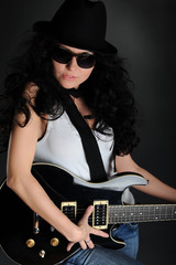 Girl in a hat with a black guitar in his hands