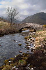 Mountain Stream flowing under a stone bridge
