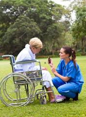 nurse giving medicine to patient in wheelchair
