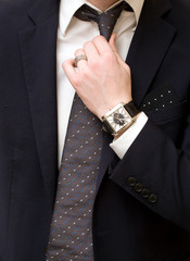 young man in an immaculate suit, manicured hands, tie a necktie