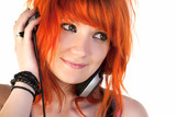 Redhead young woman holding headphones dancing