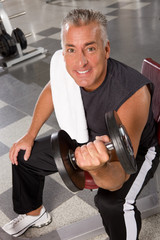 Attractive middle aged man lifting barbells