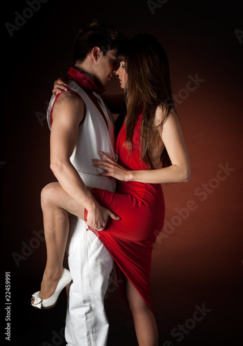 Young couple dancing embrace passion romance on dark red light