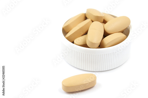 Multivitamin pills in the white plastic cap isolated on white