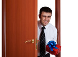 young man with gift opening the door