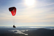 Paraglider flying over Norwegian landscape