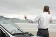 Geschäftsmann telefoniert neben Auto am Strand