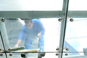 Housekeeper cleaning windows image taken from below