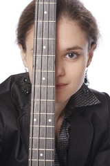 Young woman posing in studio with a black electric bass guitar